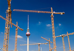 Many tower cranes at construction site in central Berlin with Television Tower to rear Germany