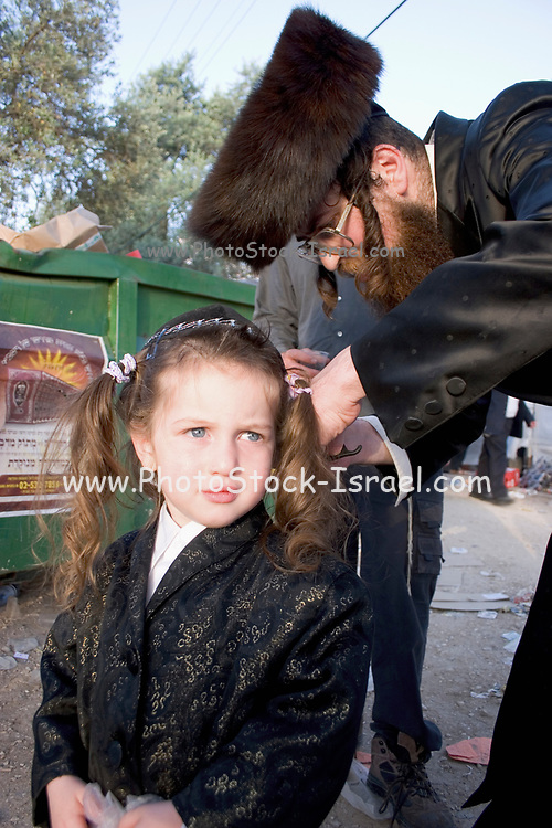 Israel, Galilee, Mount Meron, first Haircut Ceremony to 3 year old boys at Mount Meron during the lag b'omer celebrations at mount Meron. Lag B'Omer is a day for bonfire celebrations. The most famous is held at the village of Meron, near the northern city of Safed. Shimon Bar Yochai is said to be buried there, and huge crowds gather at his tomb for this very happy celebration. Since the days preceding Lag B'Omer were traditionally considered days of mourning, and therefore haircutting and shaving were not permitted, Lag B'Omer became a time for youngsters of 3 years get their first haircut.
