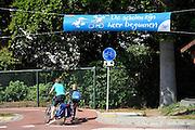 Nederland, Nijmegen, 29-8-2012Een moeder en kind fietsen langs een spandoek waarop verkeersdeelnemers erop gewezen wordt dat de scholen weer zijn begonnen.Foto: Flip Franssen/Hollandse Hoogte