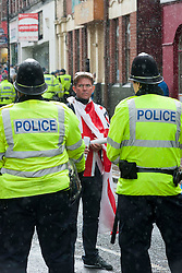 An EDL supporter wapped in the Union Flag looks back past police officers as they escort<br /> EDL members and supporters towards Rotherham Minster during Saturdays  EDL rally in South Yorkshire  in Rotherham Town Centre <br /> <br /> May 10 2014<br /> Image © Paul David Drabble <br /> www.pauldaviddrabble.co.uk