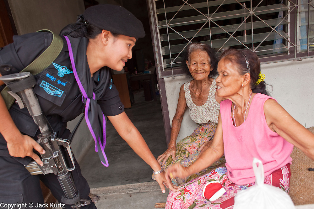 29 SEPTEMBER 2009 -- SAI BURI, PATTANI, THAILAND: Members of the Thai Rangers' womens' unit conduct a security and public outreach program in a Buddhist village in Pattani province, Thailand. The women conduct patrols close to their base and medical assistance to people in nearby villages. The 39 women in the 44th Army Ranger Regiment are the only Thai women seeing front line active duty against Moslem insurgents in Thailand's deep south provinces of Pattani, Narathiwat and Yala. All of the other women serving in Thai security services are employed as office and clerical workers. The Ranger women are based at the Ranger camp in the Buddhist village of Baan Trokbon in Sai Buri district of Pattani province. The unit was formed in 2006 after Muslims complained about the way Thai soldiers, all men, treated Muslim women at roadblocks and during security sweeps. The women are frequently called upon to back up Thai regular army units when they are expected to encounter a large number of Muslim women. At least two of the women have been killed by Muslim insurgents. The unit has both Muslim and Buddhist members. Many of the women in the unit joined after either their fathers or husbands were killed by insurgents.   PHOTO BY JACK KURTZ
