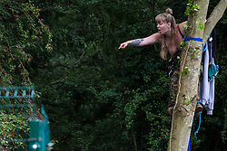 A HS2 Rebellion activist climbing a tree in Denham Country Park in order to try to protect it from works for the HS2 high-speed rail link remonstrates with a National Eviction Team enforcement agent standing inside a compound used for felling trees on 8 September 2020 in Denham, United Kingdom. Anti-HS2 activists continue to try to prevent or delay works on the controversial £106bn project for which the construction phase was announced on 4th September from a series of protection camps based along the route of the line between London and Birmingham.