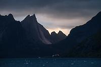 Steep mountain face of Breiflogtind rises over Kjerkfjord, Moskenesøy, Lofoten Islands, Norway