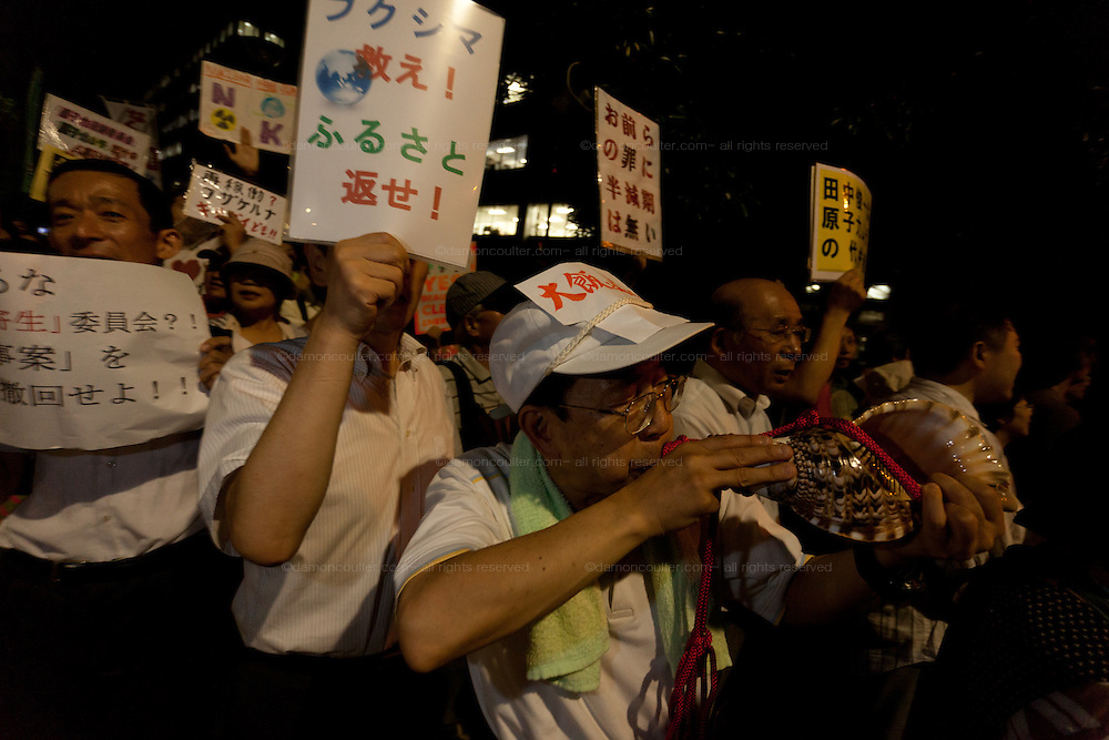 An older Japanese man blows a conch shell as protestors hold signs and banners calingl for the abolition of nuclear power in the weekly Friday night protests outside the Prime Minister's office and national diet building in Tokyo, Japan.Friday September 7th 2012