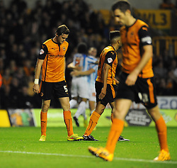 Wolverhampton Wanderers' Richard Stearman and his team mates cut dejected figures as his team go 0 - 2 as Huddersfield Town's Sean Scannell celebrates his goal in the background - Photo mandatory by-line: Dougie Allward/JMP - Mobile: 07966 386802 - 01/10/2014 - SPORT - Football - Wolverhampton - Molineux Stadium - Wolverhampton Wonderers v Huddersfield Town - Sky Bet Championship