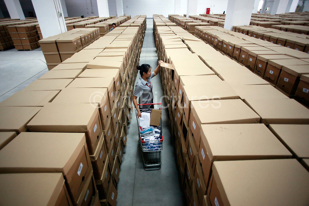 """A warehouse employee work to fill an oder at the Yihaodian warehouse and logistics center in Shanghai, China on 23 August, 2011. As online supermarkets is attracting a rapidly increasing number of young consumers, especially women, U.S. giant Walmart has acquired a minority stake in Yihaodian, or """"The Store"""", a young but very successful E-Commerce company that sells and delivers everything from food, daily household  items, electronics, and clothing."""