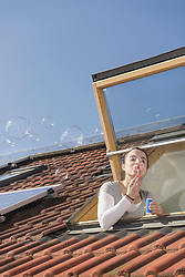 Woman blowing bubbles out of roof window with solar panels