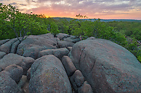 The morning sky lights up with color over Elephant Rocks State Park. This state park contains numerous large granite boulders that have been eroding for many years to make them round and smooth.<br />