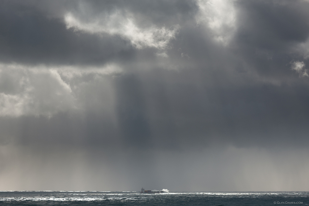 A container ship defying the odds against a stormy Atlantic ocean off the cliffs at Land's End, Cornwall.