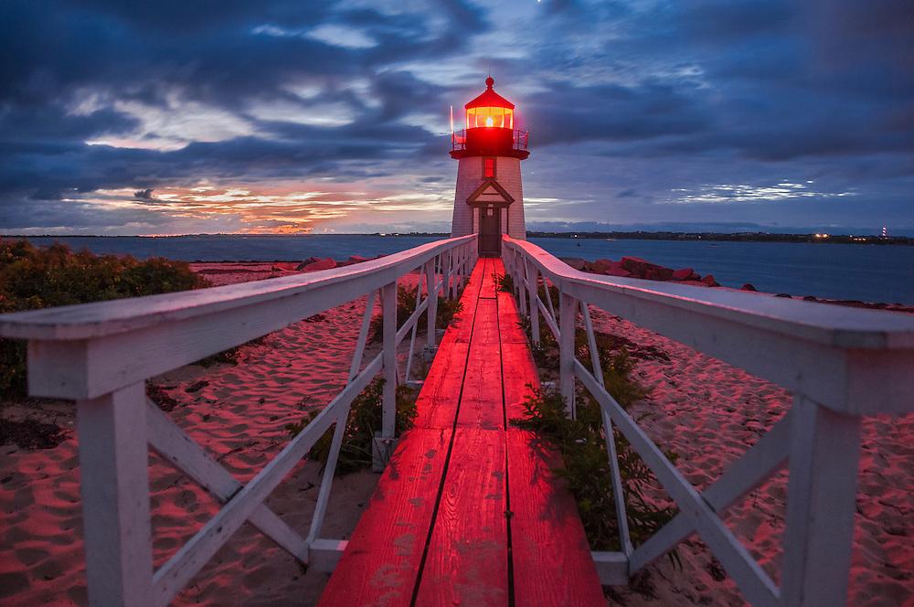 Brant Point Light lit up at pre-dawn, looking down boardwalk, Nantucket Island, MA