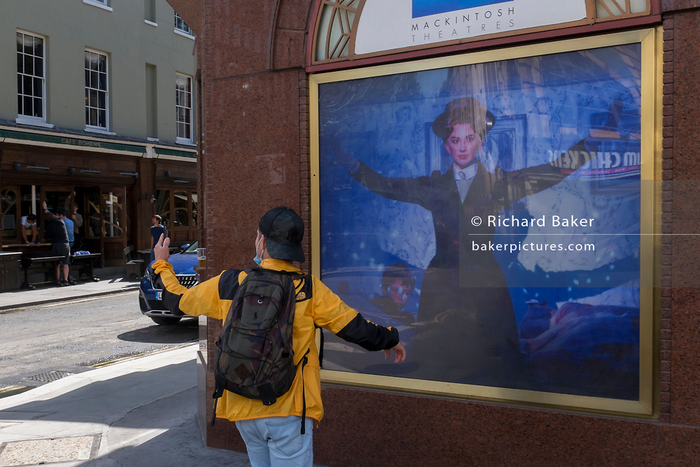 A visitor to London wearing a face mask on his chin takes a selfie of himself in front of the image of Mary Poppins outside the Prince Edward Theatre, the West End, on 2nd July 2020, in London, England.