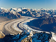Fly over Ruth Glacier and the Alaska Range in Denali National Park and Preserve, Alaska, USA. See a vast wilderness of glaciers, icy peaks, and mile deep granite gorges. Denali (20,310 feet or 6191 meters, aka Mount McKinley) is a granitic pluton uplifted by tectonic pressure while erosion has simultaneously stripped away the softer sedimentary rock above and around it.