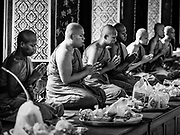 """11 APRIL 2017 - BANGKOK, THAILAND: Buddhist monks pray in Wat Chana Songkhram during a Songkran merit making service. Songkran is the traditional Thai Lunar New Year. It is celebrated, under different names, in Thailand, Myanmar, Laos, Cambodia and some parts of Vietnam and China. In most places the holiday is marked by water throwing and water fights and it is sometimes called the """"water festival."""" This year's Songkran celebration in Thailand will be more subdued than usual because Thais are still mourning the October 2016 death of their revered Late King, Bhumibol Adulyadej. Songkran is officially a three day holiday, April 13-15, but is frequently celebrated for a full week. Thais start traveling back to their home provinces over the weekend; busses and trains going out of town have been packed.     PHOTO BY JACK KURTZ"""
