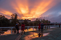 People stop to watch the amazing sun set over Glasgow's River Clyde