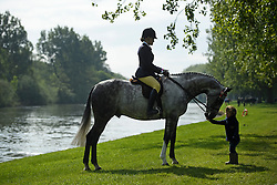 © London News Pictures. 15/05/2016. Windsor, UK. Two year old Heidi Thompson feeds Inkwell Little Mark, being ridden by her sister Megan Thompson, on the banks of the River Thames, on the final day of the 2016 Royal Windsor Horse Show, held in the grounds of Windsor Castle in Berkshire, England. This years event is part of HRH Queen Elizabeth II's 90th birthday celebrations.  Photo credit: Ben Cawthra/LNP