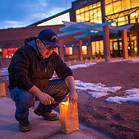 121313       Cable Hoover<br /> <br /> Navajo Nation Museum employee Nate Bitsoi lights luminarias on the walkway into the museum during the Keshmish Bazaar in Window Rock Friday.