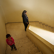 A Syrian woman and a child walking by the stairs of the refugee center in Wadi Khaled, Lebanon.