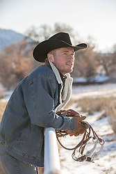 cowboy on a ranch leaning on a fence with reins in his hands
