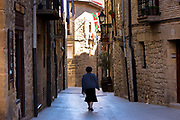 Woman walkingin Calle de Cuatro Cantones in town of Laguardia in Rioja-Alavesa area of Spain