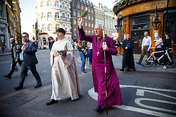 © Licensed to London News Pictures. 14/06/2017. London, UK. A bishop blesses Borough Market with holy water and prays as shop owners and traders get ready for the reopening of Borough Market in London on 14 June 2017, following a terror attack that killed 8 people over a week ago. Photo credit: Tolga Akmen/LNP