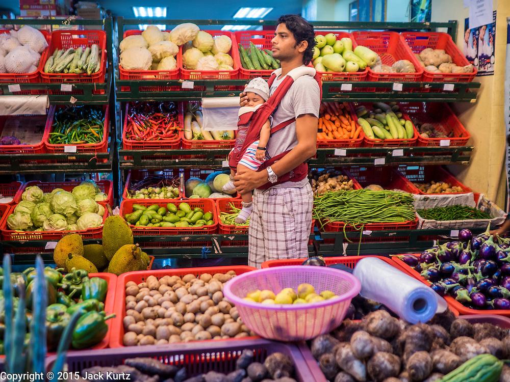 06 JUNE 2015 - KUALA LUMPUR, MALAYSIA: A man grocery shopping with his child on Jalan Tun Sambanthan in the Little India section of Kuala Lumpur.      PHOTO BY JACK KURTZ