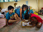 24 JANUARY 2018 - LIGAO, ALBAY, PHILIPPINES: RECHILYN BORITO, 9, works with her brother, NEL JOHN BORITO, 7, on school work in their room in a shelter in Ligao. Most of the schools in Albay province, and all of the schools near the volcano, are closed for now. The Mayon volcano continued to erupt Tuesday night and Wednesday forcing the Albay provincial government to order more evacuations. By Wednesday evening (Philippine time) more than 60,000 people had been evacuated from communities around the volcano to shelters outside of the 8 kilometer danger zone. Additionally, ash falls continued to disrupt life beyond the danger zones. Several airports in the region, including the airport in Legazpi, the busiest airport in the region, are closed indefinitely because of the amount of ash the volcano has thrown into the air.    PHOTO BY JACK KURTZ