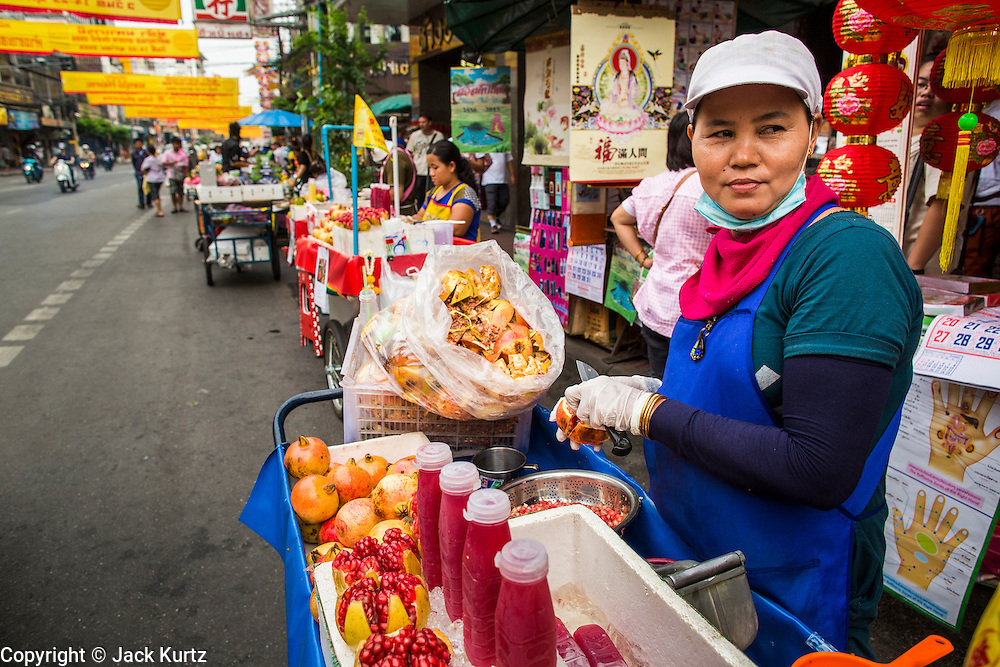 17 OCTOBER 2012 - BANGKOK, THAILAND:     A pomegranate juice vendor on Yaowarat Road in Bangkok, Thailand. The yellow banners over the road are announcing the annual Vegetarian Festival. The Vegetarian Festival is celebrated throughout Thailand. It is the Thai version of the The Nine Emperor Gods Festival, a nine-day Taoist celebration celebrated in the 9th lunar month of the Chinese calendar. For nine days, those who are participating in the festival dress all in white and abstain from eating meat, poultry, seafood, and dairy products. Vendors and proprietors of restaurants indicate that vegetarian food is for sale at their establishments by putting a yellow flag out with Thai characters for meatless written on it in red.     PHOTO BY JACK KURTZ