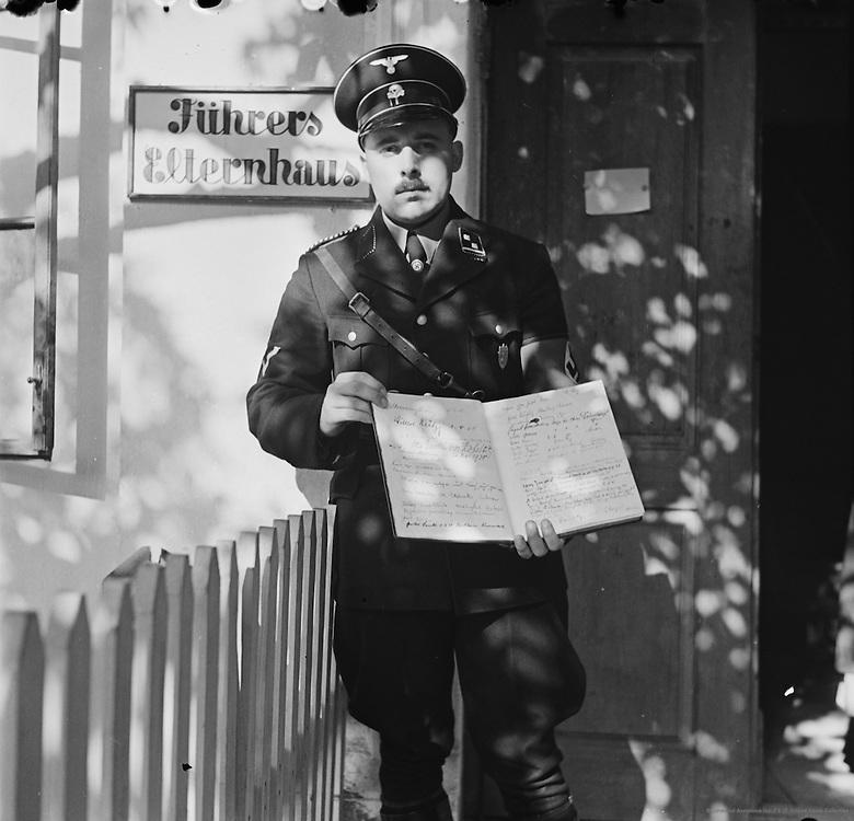 SS Officer Holding Open Book, House Where Adolf Hitler Spent His Boyhood, Leonding, Oberdonau, Upper Austria, 1937