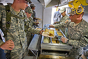 """Curtis Newcomer (left),  a soldier at the National Training Center at Fort Irwin, California, receives breakfast at the mess tent. (Curtis Newcomer is featured in the book What I Eat: Around the World in 80 Diets.)  He eats his morning and evening meals in a mess hall tent, but his lunch consists of a variety of instant meals in the form of MREs. His least favorite is the cheese and veggie omelet. """"Everybody hates that one. It's horrible,"""" he says. A mile behind him, toward the base of the mountains, is Medina Wasl, a fabricated Iraqi village (one of 13 built for training exercises), with hidden video cameras and microphones linked to the base control center for performance reviews.  MODEL RELEASED."""