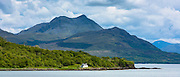 Solitary whitewashed croft cottage across the Sound of Sleat with Knoydart mountain behing, Isle of Skye,the Inner Hebrides and Western Isles in West Coast of Scotland