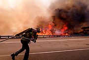 A firefighter battles a fire along the Ronald Reagan (118) Freeway in Simi Valley, Calif., Monday, Nov. 12, 2018.