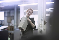 Young worker opening box while standing at printing press