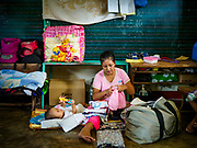 20 JANUARY 2018 - CAMALIG, ALBAY, PHILIPPINES: CRISTIN SARDALLA, sorts laundry with her infant son, CRIS GIDEON GARRA, 7 months old, at the Barangay Salugan evacuee shelter in a school in Camalig. There are about 870 people living at the shelter. They won't be allowed to move back to their homes until officials determine that Mayon volcano is safe and not likely to erupt. More than 30,000 people have been evacuated from communities on the near the Mayon volcano in Albay province in the Philippines. Most of the evacuees are staying at school in communities outside of the evacuation zone.  PHOTO BY JACK KURTZ