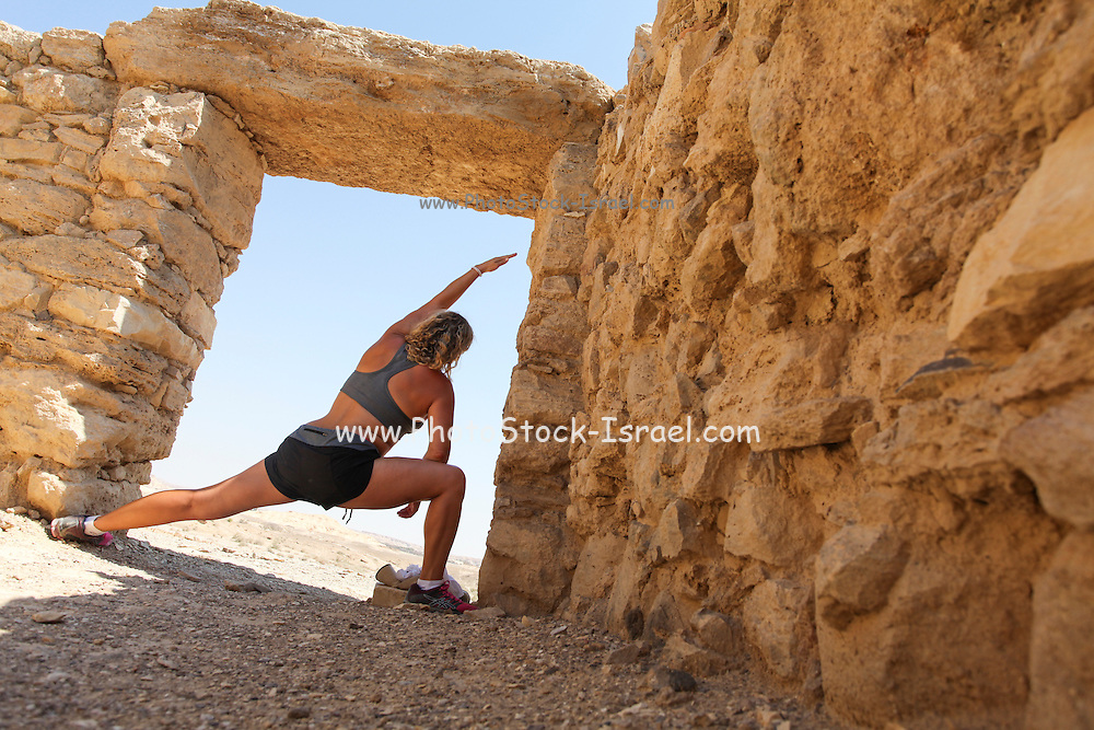 Woman worksout in ancient ruins in the desert