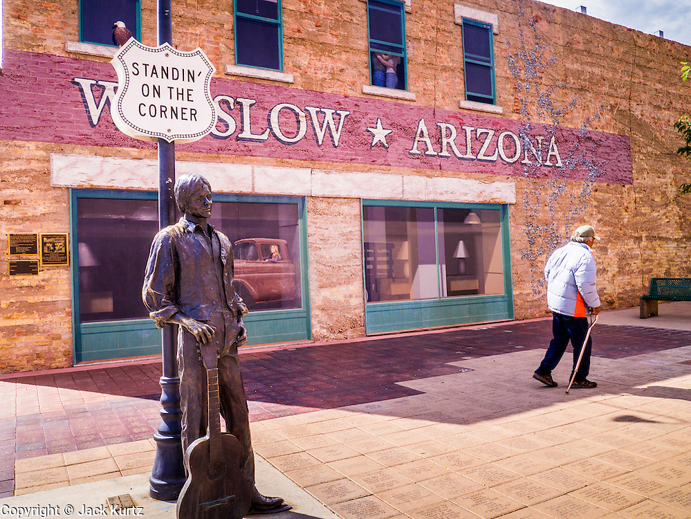 """15 JULY 2012 - WINSLOW, AZ: A Native American man walks behind the Standin' on the Corner park at the intersection of Kinsley Avenue and Second Street in Winslow, AZ. The park is based on the Eagles song, written by Jackson Browne and Glenn Frey, the second verse is """"Well, I'm a standing on a corner, In Winslow, Arizona, And such a fine sight to see. It's a girl, my lord .In a flatbed Ford, Slowin' down to take a look at me"""" The park has a statue of Jackson Browne and flatbed Ford parked nearby. There is also a mural of the scene on a wall behind the statue.       PHOTO BY JACK KURTZ"""