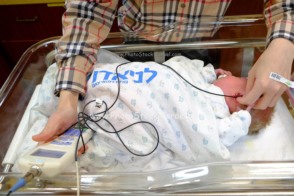 A hearing test is performed on a newborn infant baby in a maternity ward