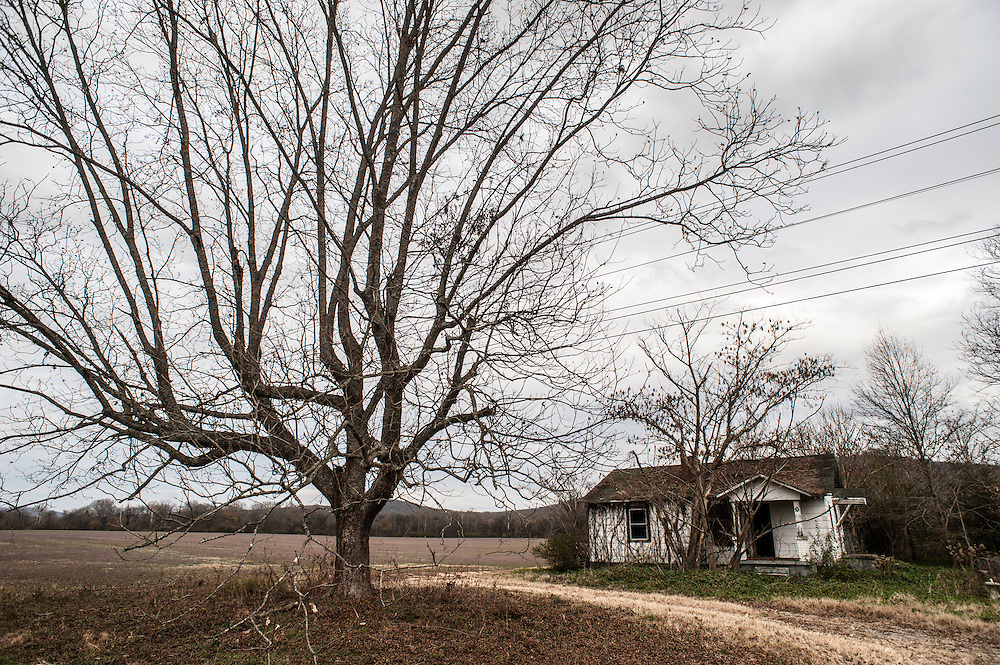An old house sits next to field in Woodville, Alabama