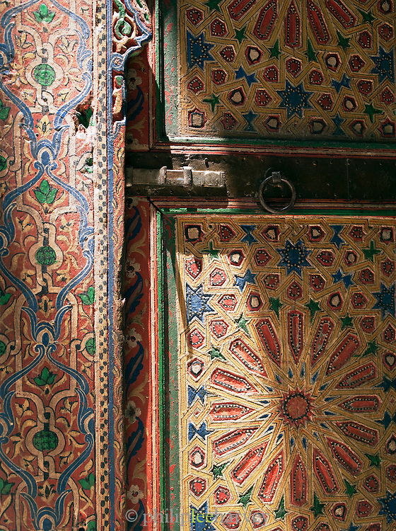 An antique door, still originally painted, at a Dar, a traditional Moroccan house, now converted to a luxury hotel in Fes, Morocco