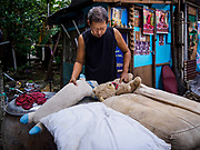 19 OCTOBER 2017 - BANGKOK, THAILAND: A man lays out his children's stuffed toys in Pom Mahakan slum in Bangkok. Most of the people living in the slum have been evicted, and the land they were living on has been turned into a volunteer center for people helping with the royal cremation, which is October 25-29, 2017. After the cremation the land will be turned into a public park.     PHOTO BY JACK KURTZ