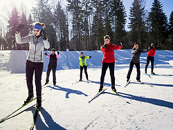 Participants learning cross country skiing course with female teacher, Black-Forest, Baden-Wuerttemberg, Germany