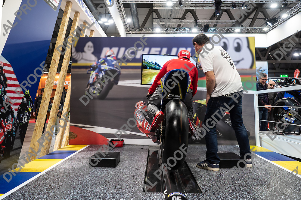 RHO Fieramilano, Milan Italy - November 07, 2019 EICMA Expo. A person being instructed before riding a motorcycle racing simulator