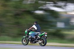 A man rides a metallic green motorcyle down a highway