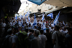 © Licensed to London News Pictures . 05/06/2016 . Jerusalem , Israel . Thousands of Jews with flags process through the Old City's Muslim district , on the way to the Western Wall , separated from residents of the Old City's Muslim district by Israeli soldiers . Israeli Jews celebrate Jerusalem Day . Photo credit : Joel Goodman/LNP