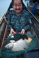 Proud Carp fisherman with catch, Poyang Ho Lake, Jiangxi province, China