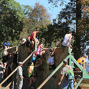 Competitors tackle a Climbing Wall during the New York Merrell Down and Dirty Obstacle Race presented by Subaru. Over 6000 competitors took part in the event which included mud pits, water crossings, slippery mountain, cargo nets, monster climb and ladder walls. The event was held at Pelham Bay Park The Bronx, New York. 29th September 2013. Photo Tim Clayton