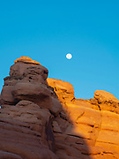 The moon rises over sandstone at dusk. Arches National Park, Moab, Utah, USA.