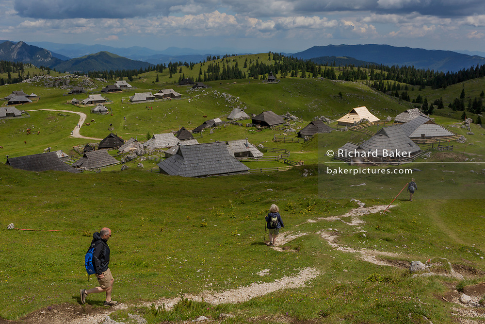 Walkers decend towards the collection of Slovenian herders' mountain huts in Velika Planina, on 26th June 2018, in Velika Planina, near Kamnik, Slovenia. Velika Planina is a mountain plateau in the Kamnik–Savinja Alps - a 5.8 square kilometres area 1,500 metres (4,900 feet) above sea level. Otherwise known as The Big Pasture Plateau, Velika Planina is a winter skiing destination and hiking route in summer. The herders' huts became popular in the early 1930s as holiday cabins (known as bajtarstvo) but these were were destroyed by the Germans during WW2 and rebuilt right afterwards by Vlasto Kopac in the summer of 1945.