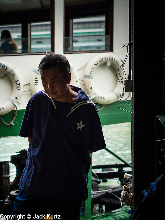 "10 AUGUST 2013 - HONG KONG:  A worker for the Star Ferry Company as a ferry sits at its mooring on the Kowloon side of Victoria Harbor. The Star Ferry, or The ""Star"" Ferry Company, is a passenger ferry service operator and tourist attraction in Hong Kong. Its principal routes carry passengers across Victoria Harbour, between Hong Kong Island and Kowloon. It was founded in 1888 as the Kowloon Ferry Company, adopting its present name in 1898.<br /> The fleet of twelve ferries currently operates two routes (four prior to April 1, 2011) across the harbour, carrying over 70,000 passengers a day, or 26 million a year. Even though the harbour is crossed by railway and road tunnels, the Star Ferry continues to provide an inexpensive mode of harbour crossing. The company's main route runs between Central and Tsim Sha Tsui. Hong Kong is one of the two Special Administrative Regions of the People's Republic of China, Macau is the other. It is situated on China's south coast and, enclosed by the Pearl River Delta and South China Sea, it is known for its skyline and deep natural harbour. Hong Kong is one of the most densely populated areas in the world, the  population is 93.6% ethnic Chinese and 6.4% from other groups. The Han Chinese majority originate mainly from the cities of Guangzhou and Taishan in the neighbouring Guangdong province.      PHOTO BY JACK KURTZ"