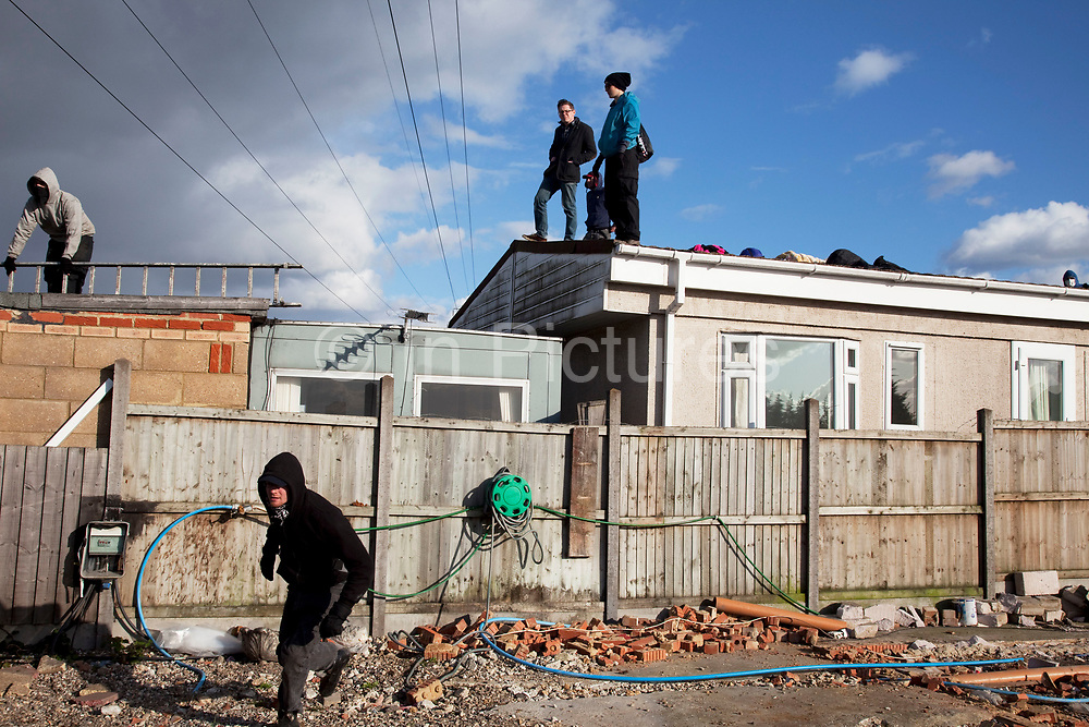 Travellers look on from a roof of one of their homes as the situation develops. Protesters who barricaded themselves above the entrance to the Dale Farm travellers' site have been removed by police as bailiffs prepare to move in. Essex Police cleared the scaffolding structure so it could be dismantled and machinery driven in by bailiffs to evict the travellers. On Wednesday night Essex Police said that over the course of the day 23 people had been arrested. Clearance of Dale Farm prior to eviction. Riot police and bailiffs were present on 19th October 2011, as a scaffolding gantry was cleared of protesters so the site could be cleared. Dale Farm is part of a Romany Gypsy and Irish Traveller site on Oak Lane in Crays Hill, Essex, United Kingdom. Dale Farm housed over 1,000 people, the largest Traveller concentration in the UK. The whole of the site is owned by residents and is located within the Green Belt. It is in two parts: in one, residents constructed buildings with planning permission to do so; in the other, residents were refused planning permission due to the green belt policy, and built on the site anyway.