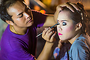 23 NOVEMBER 2013 - BANGKOK, THAILAND: Cast members of the Prathom Bunteung Silp mor lam troupe put on their makeup before a performance in Bangkok. Mor Lam is a traditional Lao form of song in Laos and Isan (northeast Thailand). It is sometimes compared to American country music, song usually revolve around unrequited love, mor lam and the complexities of rural life. Mor Lam shows are an important part of festivals and fairs in rural Thailand. Mor lam has become very popular in Isan migrant communities in Bangkok. Once performed by bands and singers, live performances are now spectacles, involving several singers, a dance troupe and comedians. The dancers (or hang khreuang) in particular often wear fancy costumes, and singers go through several costume changes in the course of a performance. Prathom Bunteung Silp is one of the best known Mor Lam troupes in Thailand with more than 250 performers and a total crew of almost 300 people. The troupe has been performing for more 55 years. It forms every August and performs through June then breaks for the rainy season.              PHOTO BY JACK KURTZ